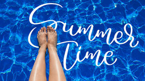Legs girl on a background of pool water and text Summer time. Calligraphy lettering hand draw.  Royalty Free Stock Photography