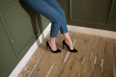 Legs of a girl in black high-heeled shoes and blue jeans stock image