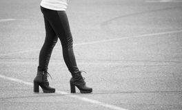 Legs of a girl in black pantyhose walking along the road Royalty Free Stock Photography