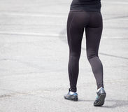 Legs of a girl in black pantyhose walking along the road Stock Photos