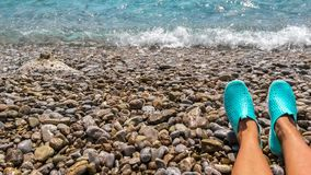 Female legs with swimming neoprene shoes. Water shoes, swimming shoe in purple neoprene on rocks in water on beach. Stock Image
