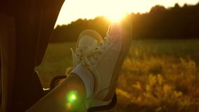 Legs of a girl in a car window, glare of the sun, riding a car on a country road. a young woman likes to travel in a car