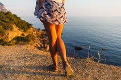 Legs of a girl in a dress on the beach stock images