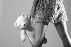 Legs of girl holding teddy bear Royalty Free Stock Photos
