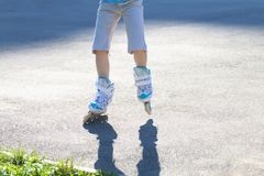 Legs of girl roller skating on playground Stock Photography