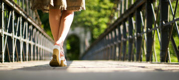 Legs of girl in skirt on bridge Royalty Free Stock Image
