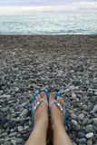 Legs in flip-flops on pebbles against the background of the sea. royalty free stock image