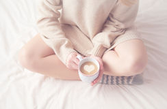Legs of girl warm woolen socks and  cup of coffee warming, winter morning in bed Stock Image