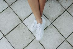 Legs of a girl in white sneakers on a gray tile royalty free stock images