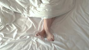 The legs of the girl who moved on the white mattress