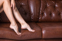 Legs of girls on a leather couch Royalty Free Stock Photography