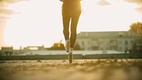 Legs of graceful young woman ballerina running on the roof on her tiptoes - sunset