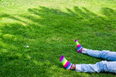 Legs on the grass with colored socks. Girl laying on the grass in the park with colored socks Royalty Free Stock Image