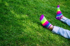 Legs on the grass with colored socks. Girl laying on the grass in the park with colored socks Royalty Free Stock Photography