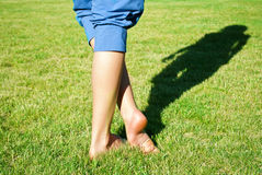 Legs on grass with shadow Stock Photos