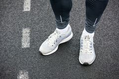 Close up of legs in running shoes standing on asphalt. Legs in gray colored running shoes standing on asphalt Royalty Free Stock Photos