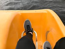 Legs in gray sport sneakers boots pedal in a yellow catamaran royalty free stock photo