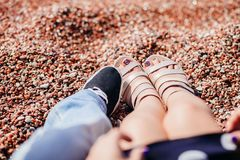 The legs of a guy and a girl in sandals in beach sand stock photo
