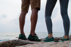 The legs of the guy and the girl standing on the kamnnisty beach, the guy and the girl sits on stones and drink from thermo mugs. Royalty Free Stock Images