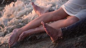 The legs of a guy in jeans and a girl in a white dress that lies in an embrace on the stones among the flowing water stock video footage
