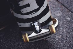 The legs of a guy in sneakers with a skateboard on the street. Close-up of skate wheel and suspension royalty free stock images