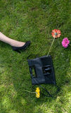 Legs, handbag and flowers on grass Royalty Free Stock Images