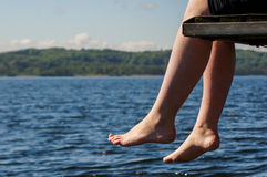 Legs hanging of a Jetty Stock Image