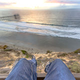 Legs hanging off the edge of a building with the ocean and pier views of the sunset Royalty Free Stock Photos