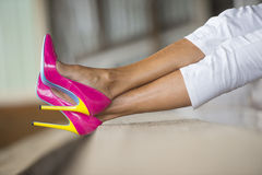 Legs and high heels lying relaxed. Concept detail close up image of woman lying in Elegant sexy pink high heel shoes, relaxed on bench, copy space, blurred Royalty Free Stock Images