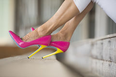 Legs and high heels shoes sitting. Concept close up image of woman sitting in Elegant sexy pink high heel stiletto shoes, relaxed on bench, copy space, blurred Royalty Free Stock Photo