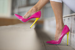 Legs and high heels sitting relaxed. Concept close up image of woman in Elegant sexy pink high heel shoes, sitting relaxed on bench, copy space, blurred Stock Photo