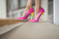 Legs and high heels standing relaxed. Concept close up image of woman sitting in Elegant extravant sexy pink high heel shoes, relaxed on bench, copy space Stock Image