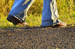 Legs hiker boots shoes woman walking country road Royalty Free Stock Photography