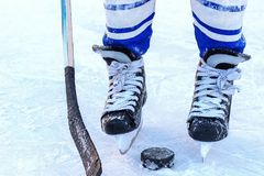 The legs of the hockey player, stick and washer close-up. The feet of a young hockey player, hockey stick and puck close-up on the background of the ice royalty free stock images