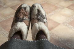 Legs in home wool fur boots. Stock Photo