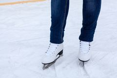 Legs of ice skater with white leather skates on ice rink, close up view stock images