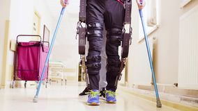 Legs of invalid in robotic exoskeleton walking through the corridor. Legs of disable man in the robotic exoskeleton walking through the corridor of the royalty free stock images