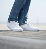 Legs in jeans and comfortable white shoes Stock Images