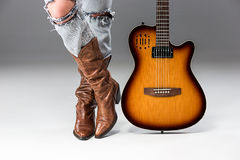 Legs in Jeans and Cowboys Boots. The female legs in ripped jeans and cowboys boots on gray studio background close up royalty free stock photo