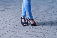 Legs in jeans on high heels Stock Images