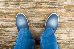 Legs in jeans and jeans shoes Royalty Free Stock Photography