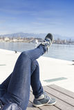 Legs in jeans pants and blue sport shoes on sea coast Royalty Free Stock Image