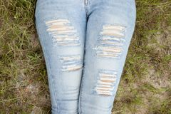 Legs of jeans are patterned. Jeans holes pants look like lacking fashion for women. and women sleep on the green grass view only leg Stock Images