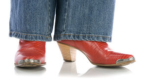 Legs in jeans wearing red cowboy boots on white. Legs in jeans wearing red cowboy boots on a white background stock images