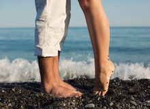 Legs of kissing couple on beach Royalty Free Stock Photo
