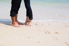 Legs of kissing couple on beach Stock Image