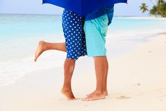 Legs of kissing couple on rainly day at tropical Stock Image