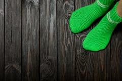 Legs knit green wool socks on wooden dark background. Stock Photo