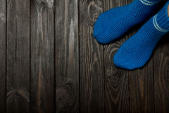 Legs knitted blue woolen socks on wooden dark background. Stock Photos