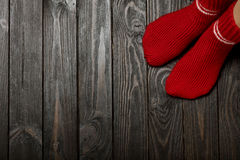 Legs knitted red wool socks on wooden dark background. Royalty Free Stock Photo
